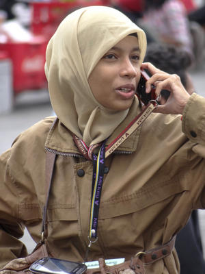 Young Muslim Woman Chats on Cellphone - Outside Retribution Museum - Jakarta - Indonesia