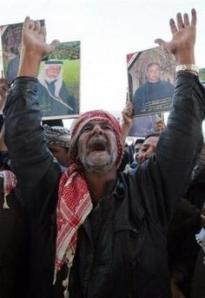 A man shouts 'God is great' as demonstrators in background